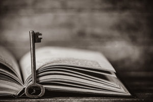 Retro Key And Open Book On Wooden Table. Image In Black And Whit